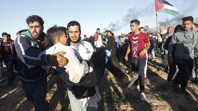 فلسطيني يحمل شاباً بعيداً عن التظاهرات على الحدود بين إسرائيل وخان يونس في جنوب قطاع غزة، في 14 ديسمبر / كانون الأول 2018. (Said Khatib/AFP)
