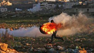 فلسطيني وسط الدخان خلال الاشتباكات مع القوات الإسرائيلية في رام الله في 14 ديسمبر، 2018. (Abbas Momani/AFP)