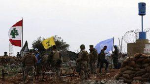 صورة التقطت من قرية ميس الجبل اللبنانية، تظهر جنود اسرائيليون يراقبون بينما جنود قوات حفظ السلام الأممية يتحدثون مع جنود لبنانيين امام علم حزب الله، 16 ديسمبر 2018 (Mahmoud ZAYYAT / AFP)