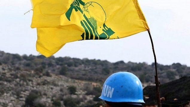 صورة تم التقاطها من قرية ميس الجبل في 16 ديسمبر، 2018، تظهر فيها جنديا تابعا لقوات الأمم المتحدة المؤقتة في لبنان (يونيفيل) يقوم بمراقبة الحدود بين لبنان وإسرائيل. على يمينه علم  لمنظمة 'حزب الله' اللبنانية الشيعية. (Mahmoud Zayyat/AFP)