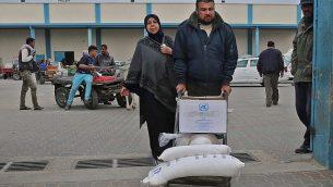 رجل فلسطيني ينقل أكياسا من الطحين خارج مركز توزيع المساعدات الذي تديره وكالة الأمم المتحدة لإغاثة وتشغيل اللاجئين الفلسطينيين في رفح في جنوب قطاع غزة، في 20 كانون الأول / ديسمبر 2018. (Said Khatib/AFP)