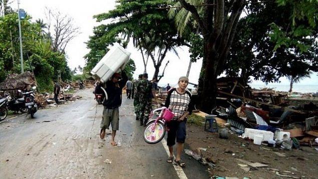 سكان يخلون منازل محطمة في كاريتا، اندونيسيا، في اعقاب تسونامي اصاب المنطقة في 22 ديسمبر نتيجة انفجار بركان اناك كراكاتوا، 23 ديسمبر 2018 (Semi/AFP)