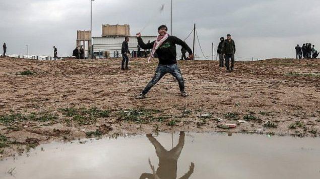 فلسطيني يقف بجوار مستنقع مياه أمطار بينما كان يستعمل مقلاعا لإلقاء جسم أثناء الاشتباكات مع القوات الإسرائيلية على طول الحدود، شرق مدينة غزة  في 28 ديسمبر / كانون الأول 2018. (Mahmud Hams/AFP)