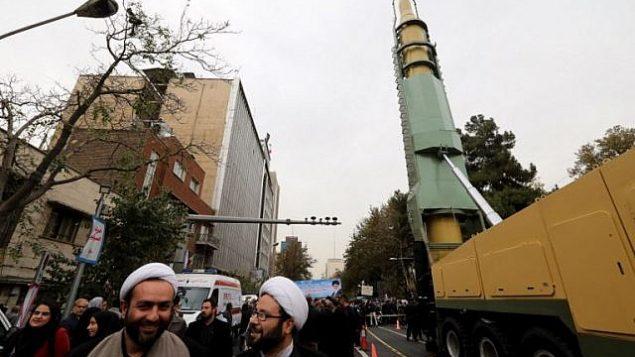 إيرانيون يحتشدون بالقرب من نسخة لصاروخ بالستي متوسط المدى خلال مظاهرت امام السفارة الأمريكية السابقة في العاصمة الإيرانية طهران، 4 نوفمبر، 2017، خلال إحياء ذكرى اقتحامها من قبل طلاب محتجين ما أدى إلى اندلاع أزمة رهائن في عام 1979.  (AFP Photo/Atta Kenare)