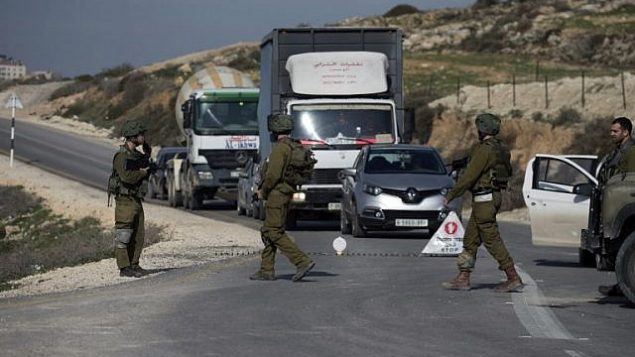 توضيحية: جنود إسرائيليون يفحصون سيارات عند نقطة تفتيش بالقرب من مدينة نابلس في الضفة الغربية في 10 يناير / كانون الثاني 2018. (Jaafar/Ashtiyeh/AFP)