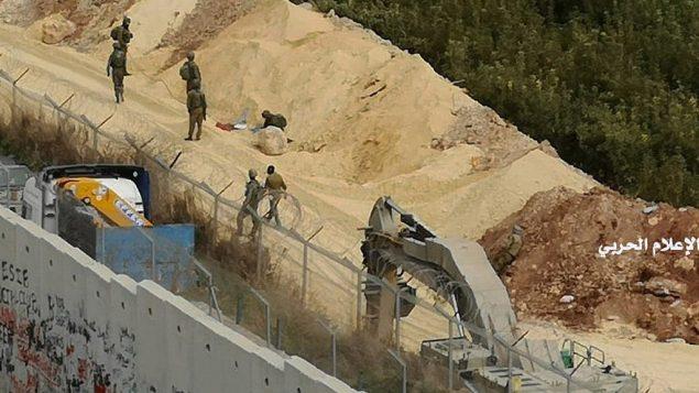 في هذه الصورة التي نشرها الإعلام الحربي المركزي التابع لحزب الله، الجيش الإسرائيلي يقوم بعلميات حفر على الحدود الإسرائيلية-اللبنانية بالقرب من الجدار الذي بنته إسرائيل مقابل قرية كفركلا اللبنانية، يوم الثلاثاء، 4 ديسمبر، 2018.  (Hezbollah Military Media via AP)