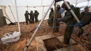 جنود إسرائيليون يقفون حول فتحة حفرة تؤدي إلى نفق يقول الجيش الإسرائيلي إن منظمة حزب الله اللبنانية قامت بحفره تحت الحدود الإسرائيلية-اللبنانية، بالقرب من المطلة، 19 ديسمبر، 2018. (AP Photo/Sebastian Scheiner)