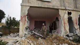 فلسطيني يفحص منزل هدمته السلطات الإسرائيلية في قرية كوبر، 16 اغسطس 2017 (AP Photo/Nasser Shiyoukhi)