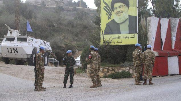قوات حفظ السلام الأمميون يقفون امام لافتة تحمل صورة قائد حزب الله حسن نصر الله، اثناء دورية في الطرف اللبناني من الحدود الإسرائيلية اللبنانية، في قرية كفر كلا الجنوبية، 4 ديسمبر 2018 (AP/Mohammed Zaatari)