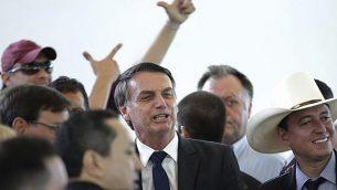الرئيس البرازيلي المنتخق جاير بولسونارو، وسط الصورة، خلال مأدبة غداء مع مغنين معروفين دعموا حملته، في 'نادي الجيش' في برازيليا، البرازيل، الثلاثاء، 11 ديسمبر، 2018. (AP/Eraldo Peres)
