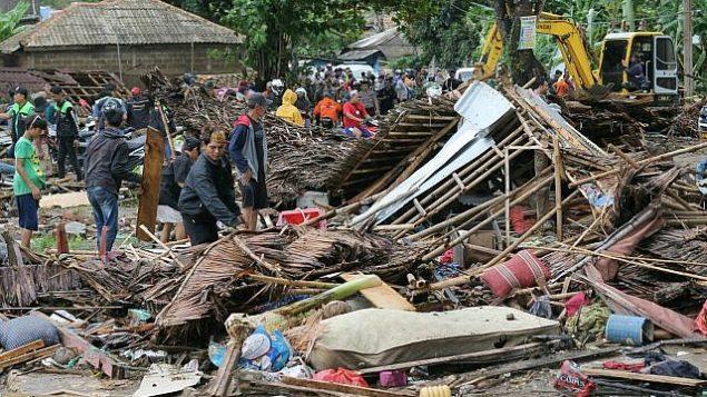 سكان يتفقدون الاضرار في بين حطام منازل دمرتها موجة تسونامي في كاريتا، اندونيسيا، 23 ديسمبر 2018 (AP Photo)