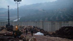 القوات الإسرائيلية تعمل بالقرب من نقطة دخول إلى أحد الأنفاق التي تم حفرها في حقل تفاح جنوبي بلدة المطلة الإسرائيلية من لبنان، 19 ديسمبر،  2018. (Judah Ari Gross/Times of Israel)
