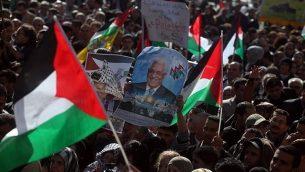 فلسطينيون يلوحون بالأعلام الفلسطينية خلال مسيرة في رام الله في 29 نوفمبر، 2012، لدعم محاولة رئيس السلطة الفلسطينية محمود عباس الحصول على اعتراف بالدولة الفلسطينية في الأمم المتحدة. (Issam Rimawi/Flash90)