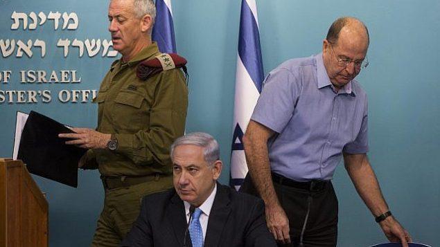 رئيس الوزراء بينيامين نتنياهو، وسط الصورة، ووزير الدفاع حينذاك موشيه يعالون، من اليمين، ورئيس هيئة أركان الجيش الإسرائيلي حينذاك بيني غانتس، من اليسار، في مؤتمر صحفي في مكتب رئيس الوزراء في القدس، 27 أغسطس، 2014. (Yonatan Sindel/Flash90)