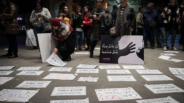 وضع إعلانات نعي تحمل أسماء نساء من ضحايا العنف على الأرض في ميدان 'تسيون' في القدس خلال تظاهرة احتجاجا على العنف ضد النساء في 27 نوفمبر، 2018.   (Hadas Parush/Flash90)