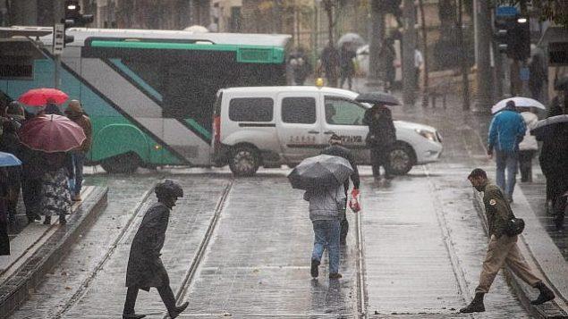 الناس يسيرون في شارع يافا المبتل بالأمطار في القدس في 6 ديسمبر، 2018. (Yonatan Sindel / Flash90)