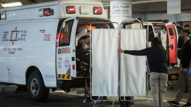 عناصر امن واسعاف اسرائيليون يخلون امرأة اسرائيلية من سيارة اسعاف في مستشفى شعاريه تسيديك في القدس، بعد اصابتها بإصابات بالغة في هجوم اطلاق نار في مستوطنة عوفرا بالضفة الغربية، 9 ديسمبر 2018 (Hadas Parush/Flash90)