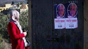 سيدة فلسطينية تمر من أمام ملصقات تظهر  صورة للرئيس الفلسطيني محمود عباس مرفقة بعبارة 'اغتيال ممولي الإرهاب' في حاجز حوارة، جنوب مدينة نابلس في الضفة الغربية، 11 ديسمبر، 2018. (Nasser Ishtayeh/Flash90)