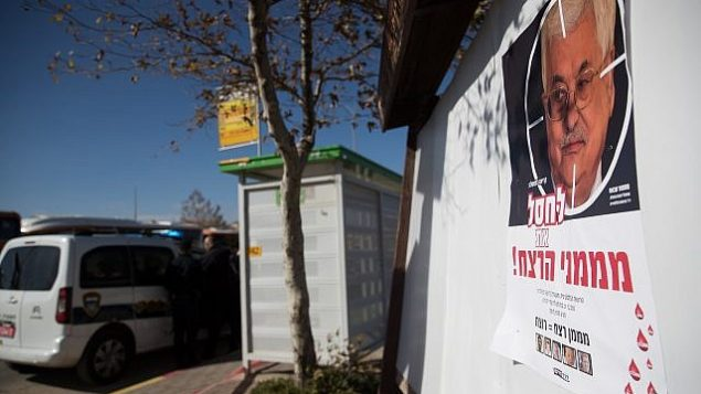 """A poster showing Palestinian President Mahmud Abbas with a text reading """"Eliminate the sponsers of murder"""" is hanging on a bus station at the entrance to the Israeli settlement of Adam, in the central West Bank on December 11, 2018. (Yonatan Sindel/Flash90)"""