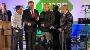 رئيس الوزراء بينيامين نتنياهو (الثالث من اليسار) يقوم بقص الشريط في مراسم افتتاح تقاطع طرق جديد في مستوطنة آدم في وسط الضفة الغربية، 11 ديسمبر، 2018. (Jacob Magid/Times of Israel)