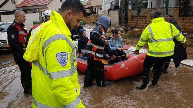 رجال الإنقاذ يستخرجون الإسرائيليين من منازلهم التي غمرتها الفيضانات في أحيعيز بوسط إسرائيل، بعد سقوط أمطار غزيرة على البلاد في 7 ديسمبر 2018 (الشرطة الإسرائيلية)