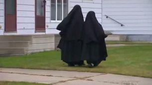 فتاتان من طائفة 'ليف طاهور' تسيران في بلدة تشاتام، في مقاطعة أونتاريو الكندية، في ديسمبر 2013.  (screen capture: YouTube)