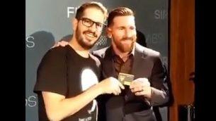 نجم كرة القدم الأرجنتيني ليونيل ميسي (إلى اليمين) يستلم بطاقة عضوية نادي بيتار القدس من مالك النادي موشيه حوغغ في حدث في برشلونة، إسبانيا، في ديسمبر 2018. (لقطة شاشة: تويتر)