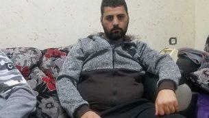 محمد العباسي (25 عاما) يجلس في غرفة المعيشة في منزل أحد أقربائه في سلوان، 23 ديسمبر، 2018. (Adam Rasgon/Times of Israel)