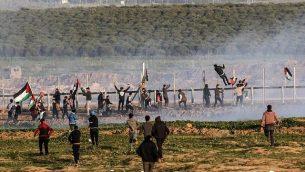 متظاهرون فلسطينيون يحاولون تسلق السياج الحدودي مع إسرائيل خلال مواجهات اندلعت بعد مظاهرات على طول الحدود في شرق مدينة غزة، 4 يناير، 2019. (Said Khatib/AFP)