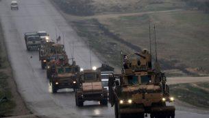 هذه الصورة التي تم التقاطها في 30 ديسمبر، 2018 تظهر قافلة مركبات عسكرية أمريكية تسير على طريق في مدينة منبج في شمال سوريا.  (Photo by Delil SOULEIMAN / AFP)