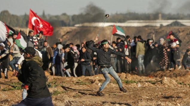 متظاهر فلسطيني يستخدم مقلاع لرشق حجارة باتجاه القوات الإسرائيلية في الطرف الثاني من السياج الحدودي، خلال اشتباكات عند الحدود بين اسرائيل وقطاع غزة، 11 يناير 2019 (Mahmud Hams/AFP)