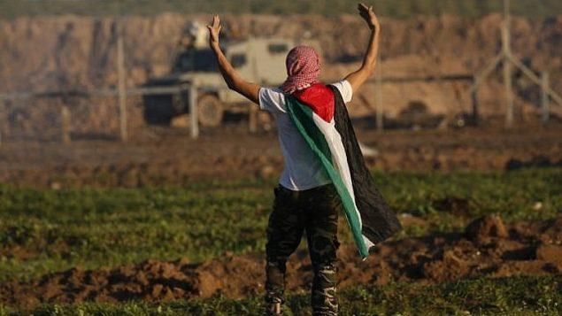متظاهر يضع على كتفيه بالعلم الفلسطيني خلال مواجهات مع القوات الإسرائيلية بعد مظاهرة على الحدود مع إسرائيل في شرق مدينة غزة، 18 يناير، 2019. (Said KHATIB / AFP)
