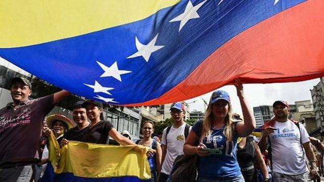 أنصار المعارضة في فنزويلا يشاركون في مسيرة بمناسبة ذكرى ثورة عام 1958 التي أطاحت بالدكتاتورية العسكرية في كاركاس، 23 يناير، 2019.  (Federico Parra / AFP)