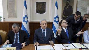 رئيس الوزراء بينيامين نتنياهو (وسط الصورة)، سكرتير الحكومة تساحي برافرمان (من اليمين)، ووزير السياحي ياريف لافين (من اليسار)، خلال الجلسة الأسبوعية للحكومة في مكتب رئيس الوزراء في القدس، 27 يناير، 2019. (ABIR SULTAN / POOL / AFP)