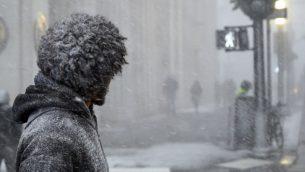 رجل ينتظر عبور الشارع اثناء تساقط الثلج في مانهاتن، نيويورك، 30 يناير 2019 (JOHANNES EISELE / AFP)
