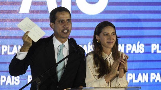 """زعيم المعارضة الفنزويلية الذي أعلن عن نفسه """"رئيسا بالوكالة""""، خوان غوايدو (من اليسار) يتحدث وهو يقف إلى جانب زوجته، فابيانا روزاليس، خلال عؤض لخطته الحكومة، في قاعة جامعة فنزويلا المركزية، 31 يناير، 2019.  (Photo by Federico Parra / AFP)"""