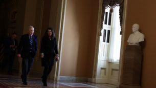 قائد الاغلبية في مجلس الشيوخ ميتش مكونيل، يمشي باتجاه قاعة مجلس الشيوخ مع سكرتارية الاغلبية لاوري دوف، 28 يناير 2019، في مبنى الكابيتول في واشنطن (Alex Wong/Getty Images/AFP)