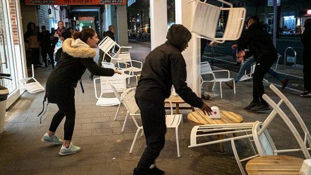 متظاهرون إثيوبيون إسرائيليون يقومون بتخريب مقهى على جانب الطريق في جادة 'ابن غابيرول' في تل أبيب، 20 يناير، 2019. (Luke Tress/Times of Israel)