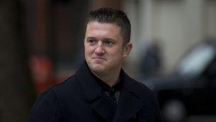 تومي روبنسون، القائد السابق لرابطة الدفاع الإنجليزية اليمينية المتطرفة، يسير أمام ضباط الشرطة وهو يغادر بعد مثوله أمام محكمة الصلح في وستمنستر في لندن، 16 أكتوبر / تشرين الأول 2013. (AP Photo / Matt Dunham)