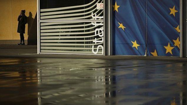 """امرأة تدخن خارج مقر المفوضية الأوروبية في بروسكل، الإثنين، 14 يناير، 2019. في رسالة إلى رئيسة الوزراء البريطانية تيريزا ماي تم نشرها يوم الإثنين، قال رئيس المجلس الأوروبي دونالد توسك ورئيس المفوضية الأوروبية جان كلود يونكر إن دعم الإتحاد الأوروبي """"سيكون فقط متوفرا ما دامت هناك حاجة ماسة إليه"""". (AP Photo/Francisco Seco)"""