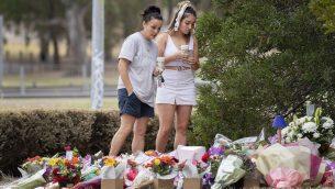 سيدتان تقفان امام ازهار في موقع العثور على جثمان الطالبة العربية الإسرائيلية آية مصاروة في ملبورن، استراليا، 18 يناير 2019 (Ellen Smith/AAP Image via AP)