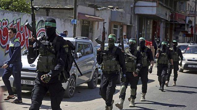 مسلحون ملثمون من كتائب عز الدين القسام، الجناح العسكري لحركة حماس، يسيرون مع أسلحة خلال مناورة واسعة النطاق في قطاع غزة، 25 مارس، 2018.  (AP Photo/ Khalil Hamra)
