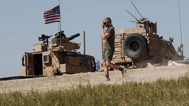 جندي أميركي يمشي في موقع تم تثبيته حديثا، بالقرب من خط المواجهة المتوتر بين مجلس منبج العسكري المدعوم أمريكيا والمقاتلين المدعومين من قبل تركيا في منبج، شمال سوريا، 4 أبريل / نيسان 2018. (AP/Hussein Malla)