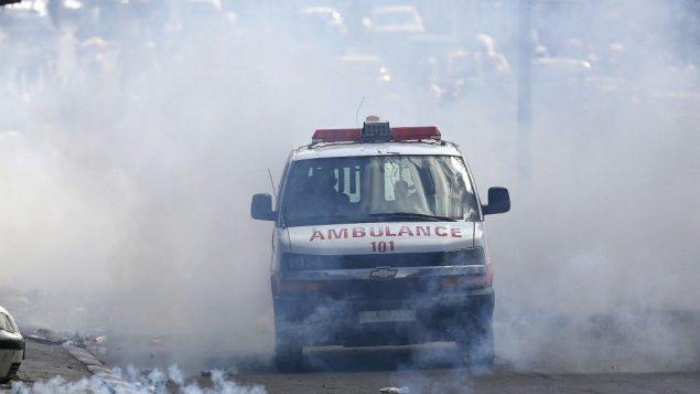 سيارة اسعاف فلسطينية تخرج مع غمامة غاز مسيل للدموع خلال اشتباكات بين فلسطينيين وقوات اسرائيلية في مدينة بيت لحم بالضفة الغربية، 15 مايو 2018 (AP Photo/Majdi Mohammed)