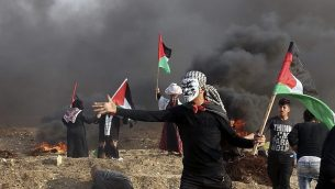 فلسطينيون يحملون اعلام بينما يتصاعد دخان اطارات مشتعلة خلال اشتباكات بالقرب من الحدود بني قطاع غزة واسرائيل، 9 نوفمبر 2018 (AP Photo/Adel Hana)