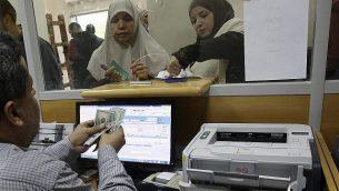 موظفة حكومية معينة من قبل حماس في غزة توقع على وثيقة للحصول على 50% من راتبها المتأخر من أموال تبرعت بها قطر، مع انتظار الآخرين في الطابور، في مكتب البريد الرئيسي في غزة، 7 ديسمبر، 2018.  (AP Photo/Adel Hana)