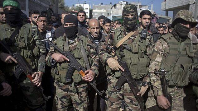 مسلحون ملثمون تابعون لحركة 'حماس' خلال جنازة محمود النباهين (24 عاما) في مخيم البريج، في وسط قطاع غزة، 23 يناير، 2019. (AP Photo/ Khalil Hamra))