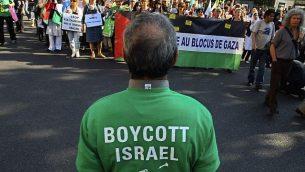 متظاهرون يهتفون بشعارات خلال مسيرة في العاصمة الفرنسية باريس، 3 يونيو، 2010، في احتجاج ضد اعتراض إسرائيل لأسطول سفن متوجه إلى غزة× في مقدمة الصورة رجل يرتدي قميصا يحمل دعوة إلى مقاطعة إسرائيل.  (Jacques Brinon/ AP)