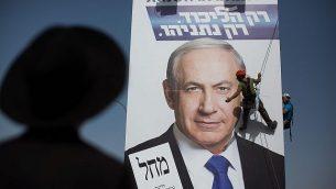 رجل حريدي يراقب عمالا يقومون بتعلق ملصق دعاية إنتخابية لرئيس الوزراء بينيامين نتنياهو عند مدخل مدينة القدس في 11 مارس، 2015. (Yonatan Sindel/FLASh90)