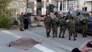 جنود إسرائيليون يقفون بالقرب من جثة مشتبه به بمحاولة تنفيذ هجوم طعن أطلق الجنود النار عليها بالقرب من مستوطنة كريات أربع في الضفة الغربية، 11 يناير، 2018. (Screen Capture: Twitter)